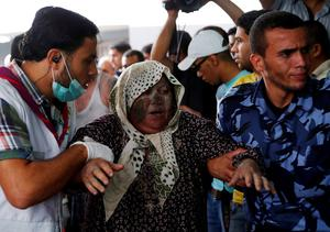Palestinians escort a wounded woman in the emergency room of Shifa hospital in Gaza City, northern Gaza Strip, Sunday, July 20, 2014. (AP Photo/Lefteris Pitarakis)