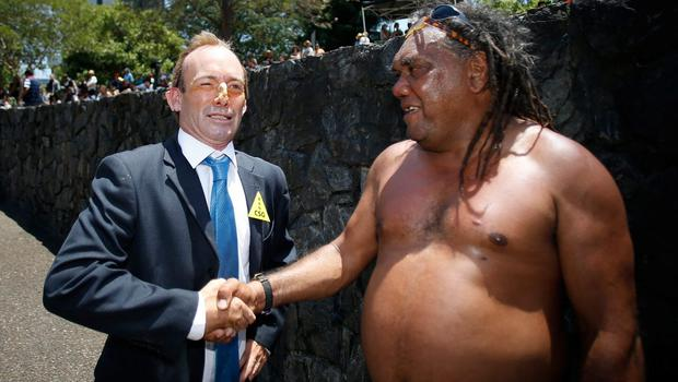 A man depicting Australian Prime Minster Tony Abbott greets an Indigenous Australian during a protests against G20 leaders on November 15, 2014 in Brisbane, Australia (Photo by Daniel Munoz/Getty Images)