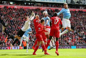 Javi Garcia of Manchester City heads at goal past the dive of Simon Mignolet of Liverpool during the Barclays Premier League match between Liverpool and Manchester City at Anfield on April 13, 2014 in Liverpool, England.  (Photo by Alex Livesey/Getty Images)