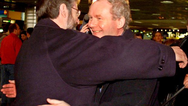 File photo dated 15/03/2000 of Sinn Fein President Gerry Adams (left) and Martin McGuinness embracing at Dublin Airport. PA