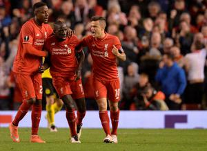 Liverpool's French defender Mamadou Sakho (C) celebrates with Liverpool's Belgian striker Divock Origi (L) and Liverpool's Brazilian midfielder Philippe Coutinho after scoring during the UEFA Europa league quarter-final second leg football match between Liverpool  and Borussia Dortmund at Anfield stadium in Liverpool on April 14, 2016. / AFP PHOTO / OLI SCARFFOLI SCARFF/AFP/Getty Images