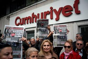 """People gather to protest the jailing of opposition Cumhuriyet newspaper's editor-in-chief Can Dundar and Ankara representative Erdem Gul, in Istanbul, Turkey, Friday, Nov. 27, 2015. The protesters accused the government of silencing critics and attempting to cover-up a scandal after Dundar and Gul were jailed on terror and espionage charges for their reports on alleged Turkish arms smuggling to Syria. Dundar and Gul were sent to a prison in Istanbul late on Thursday, accused of willingly aiding a terror organization and revealing state secrets, amid deepening concerns over media freedoms in the country that aspires to join the European Union. The headline reads: """" Black day of the press.""""(Can Erok/Cumhuriyet via AP)"""
