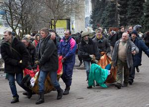 Bodies of killed anti-government protesters are carried in central Kiev, Ukraine, Thursday, Feb. 20, 2014. A brief truce in Ukraine's embattled capital failed Thursday, spiraling into fierce clashes between police and anti-government protesters. (AP Photo/Darko Bandic)