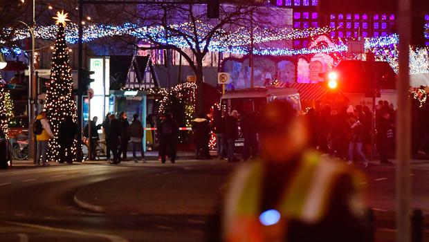 People stand at the scene where a truck speeded into a christmas market in Berlin, on December 19, 2016 killing nine persons and injuring at least 50 people. / AFP PHOTO / John MACDOUGALLJOHN MACDOUGALL/AFP/Getty Images