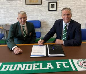 Colin Nixon signs his contract at Wilgar Park after taking over as manager of Dundela.