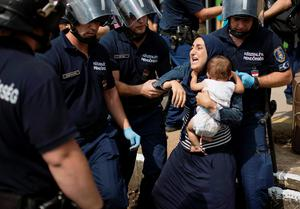 TOPSHOTS A migrant family is arrested by local police after their local train coming from Budapest and heading to the Austrian border has been stopped in Bicske, west of the Hungarian capital on September 3, 2015. The train carrying between 200 and 300 migrants left Budapest's main international train station after authorities re-opened the station to migrants as the EU is grappling with an unprecedented influx of people fleeing war, repression and poverty in what the bloc has described as its worst refugee crisis in 50 years. AFP PHOTO / ISTVAN BIELIKISTVAN BIELIK/AFP/Getty Images