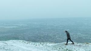 Snow falling over Belfast as a lone hill climber walks along Cave Hill. (Photo by Charles McQuillan/Getty Images)