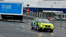 Intimidated: Police patrol the port of Larne after workers were threatened
