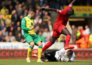 Liverpool's Simon Mignolet saves at the feet of team mate Mamadou Sakho and Norwich City's Gary Hooper during the Barclays Premier League match at Carrow Road, Norwich.