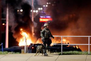 Police arrive at a business Tuesday, Nov. 25, 2014, in Dellwood, Mo, as used cars in a parking lot next to the building burn. A grand jury has decided not to indict Ferguson police officer Darren Wilson in the death of Michael Brown, the unarmed, black 18-year-old whose fatal shooting sparked sometimes violent protests. (AP Photo/Charlie Riedel)