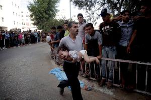 A Palestinian man rushes a child, injured from an Israeli Strike in Shijaiyah neighborhood, to an emergency room at Shifa Hospital, in Gaza City, Wednesday, July 30, 2014. (AP Photo/Khalil Hamra)