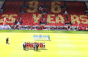 Players from both teams line up for a minutes silence in front of fans in the Kop displaying cards to form a message in remembrance of the 96 Liverpool fans that lost their lives in the Hillsborough disaster during the Barclays Premier League match at Anfield, Liverpool. Photo: Peter Byrne/PA