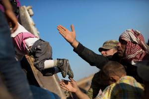 SANLIURFA, TURKEY - OCTOBER 01:  A man lifts a child into the back of a truck after crossing the border from Syria into Turkey on October 1, 2014 near Suruc, Turkey. Kurdish troops are engaged in a battle against fighters of the Islamic State (IS, also called ISIS and ISIL) to defend the strategic nearby Kurdish border town of Kobani (also called Ayn Al-Arab), which ISIS has surrounded on three sides. The Turkish Parliament is due to vote on a measure on October 2, which would allow Turkish ground forces to enter Syria, creating a buffer zone to protect fleeing refugees from the ISIS advance.  (Photo by Carsten Koall/Getty Images)