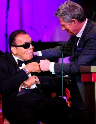This file photo taken on March 24, 2012 shows Director David Foster (R) bumping fists with boxing legend Muhammad Ali on stage at the Muhammad Ali's Celebrity Fight Night XVIII in Phoenix, Arizona. The event supports the fight against Parkinson's disease and this year also celebrates Ali's 70th birthday.   Heavyweight boxing legend Muhammad Ali, an icon of the 20th Century whose fame transcended the sport during a remarkable career that spanned three decades, died June 3, 2016, his family said. / AFP PHOTO / ROBYN BECKROBYN BECK/AFP/Getty Images
