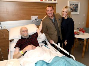 Celtic manager Brendan Rodgers with his fiancee Charlotte Searle and Glasgow Rangers fan Billy during his visit to the NI Hospice