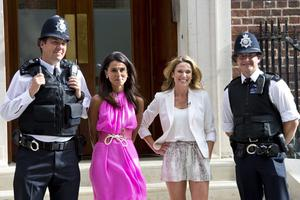 ABC News correspondents Amy Robach and Lama Hasan pose next to police officers outside the Lindo Wing as the UK prepares for the birth of the first child of The Duke and Duchess of Cambridge (Photo by Ben A. Pruchnie/Getty Images)