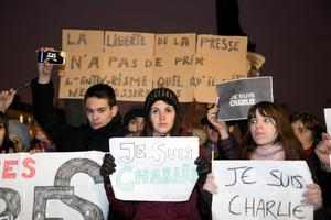 PARIS, FRANCE - JANUARY 07: People hold signs saying 'Je suis Charlie' as crowds gather at 'Place de la Republique' for a vigil following the terrorist attack earlier today on January 7, 2015 in Paris, France. Twelve people were killed, including two police officers, as two gunmen opened fire at the offices of the French satirical publication Charlie Hebdo.  (Photo by Marc Piasecki/Getty Images)