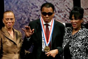 In this Sept. 13, 2012, file photo, retired boxing champion Muhammad Ali, center, waves alongside his wife Lonnie Ali, left, and his sister-in-law Marilyn Williams, right, after receiving the Liberty Medal during a ceremony at the National Constitution Center in Philadelphia.  Ali, the magnificent heavyweight champion whose fast fists and irrepressible personality transcended sports and captivated the world, has died according to a statement released by his family Friday, June 3, 2016. He was 74. (AP Photo/Matt Slocum, File)