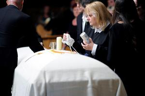 Jackie Donohoe places items on top of her daughter's casket during a service for Olivia Burke, 21, and Ashley Donohoe, 22, at St. Joseph Catholic Church in Cotati, Calif., Saturday, June 20, 2015.  The two woman were among the several people killed on Tuesday when a balcony snapped off the fifth floor of a Berkeley apartment building during a birthday party. (AP Photo/Michael Short)