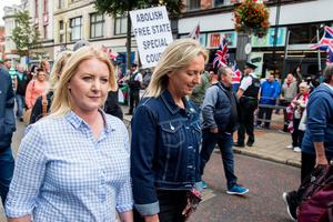 Sharon Jordan (nee Rafferty) (left) and Mandy Duffy (right) with Irish Republicans supporters walk pass a loyalist counter protest during an Anti Internment League Parade through Belfast. Saturday 11th  August 2018