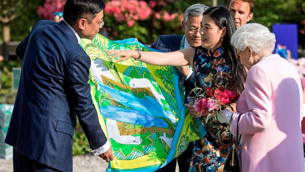 Britain's Queen Elizabeth II (R) is presented with a Chinese silk scarf depicting two whales after she looked at the Chinese show garden at the 2018 Chelsea Flower Show in London on May 21, 2018. The Chelsea flower show, held annually in the grounds of the Royal Hospital Chelsea, opens to the public on May 22.  / AFP PHOTO / POOL / RICHARD POHLERICHARD POHLE/AFP/Getty Images