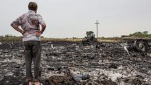 GRABOVKA, UKRAINE - JULY 18: A man looks at debris from an Malaysia Airlines plane crash on July 18, 2014 in Grabovka, Ukraine. Malaysia Airlines flight MH17 travelling from Amsterdam to Kuala Lumpur has crashed on the Ukraine/Russia border near the town of Shaktersk. The Boeing 777 was carrying 280 passengers and 15 crew members. (Photo by Brendan Hoffman/Getty Images)