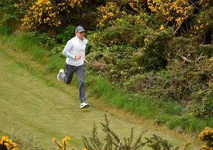 NEWCASTLE, NORTHERN IRELAND - MAY 27:  Rory McIlroy of Northern Ireland runs past gorse bushes to get to the 4th tee during the Pro-Am round prior to the Irish Open at Royal County Down Golf Club on May 27, 2015 in Newcastle, Northern Ireland.  (Photo by Ross Kinnaird/Getty Images)