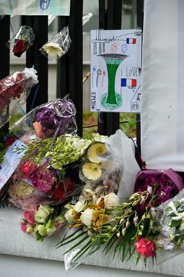 A message and flowers are seen in tribute to the victims of Paris attacks outside the French Embassy in Singapore on November 16, 2015. Islamic State jihadists claimed a series of coordinated attacks by gunmen and suicide bombers in Paris on November 13 that killed at least 129 people in scenes of carnage at a concert hall, restaurants and the national stadium. AFP PHOTO / ROSLAN RAHMANROSLAN RAHMAN/AFP/Getty Images