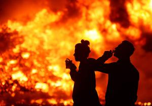 A couple walk past the 11th night bonfire at the New Mossley housing estate on July 12, 2015 in Belfast, Northern Ireland. New Mossley is widely recognised as the largest bonfire in the province. (Photo by Charles McQuillan/Getty Images)