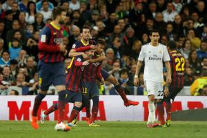 Barcelona's Lionel Messi from Argentina, left, second left, celebrates his goal with teammates next to  Real's Angel Di Maria, second right, during a Spanish La Liga soccer match between Real Madrid and FC Barcelona at the Santiago Bernabeu  stadium in Madrid, Spain, Sunday, March 23, 2014. (AP Photo/Andres Kudacki)