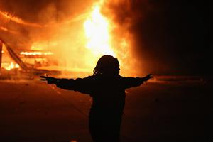 FERGUSON, MO - NOVEMBER 24:  A demonstrator celebrates as a business burns after it was set on fire during rioting following the grand jury announcement in the Michael Brown case on November 24, 2014 in Ferguson, Missouri. Ferguson has been struggling to return to normal after Brown, an 18-year-old black man, was killed by Darren Wilson, a white Ferguson police officer, on August 9. His death has sparked months of sometimes violent protests in Ferguson. A grand jury today declined to indict officer Wilson.  (Photo by Scott Olson/Getty Images)