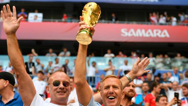 Two England fans rise a replica of the World Cup trophy before the Russia 2018 World Cup quarter-final football match between Sweden and England at the Samara Arena in Samara on July 7, 2018. / AFP PHOTO / YURI CORTEZ / RESTRICTED TO EDITORIAL USE - NO MOBILE PUSH ALERTS/DOWNLOADS YURI CORTEZ/AFP/Getty Images