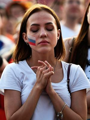 A Russia's fan reacts while watching on a giant screen in the Fans Zone of Ekaterinburg, the Russia 2018 World Cup Group A football match between Uruguay and Russia on June 25, 2018. / AFP PHOTO / Anne-Christine POUJOULATANNE-CHRISTINE POUJOULAT/AFP/Getty Images