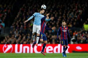 Manchester City's David Silva, left, jumps for the ball with Barcelona's Ivan Rakitic during a Champions League round of 16 second leg, soccer match between FC Barcelona and Manchester City at Camp Nou stadium, in Barcelona, Spain, Wednesday, March 18, 2015. (AP Photo/Emilio Morenatti)