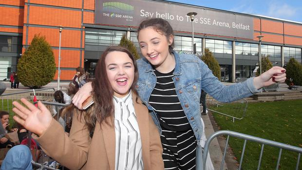 Press Eye - Belfast - Northern Ireland - 21st October 2015  One Direction fans queue up at the SSE Arena in Belfast ahead of tonight's concert.  The boy band, who are playing three nights in Belfast, cancelled last nights gig at the last minute.  The group made an announcement around lunch time to say they were going ahead with the rest of the shows and are rescheduling the canceled performance to Friday night.   Left to right.  Fans Niamh O'Neill and Maeve Devlin pictured at the SSE Arena.  Picture by Jonathan Porter/PressEye