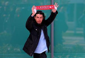 WARRINGTON, ENGLAND - APRIL 26:  A relative of Hillsborough victims holds up a Liverpool scarf as he departs Birchwood Park after hearing the conclusions of the Hillsborough inquest on April 26, 2016 in Warrington, England. The fresh inquests into the 1989 Hillsborough disaster, in which 96 football supporters were crushed to death, concluded on April 26, 2016 with a verdict of unlawful killing, after the initial verdicts were quashed. Relatives of Liverpool supporters who died in Britain's worst sporting disaster gathered in the purpose-built court to hear the jury's verdict in Warrington after a 25 year fight to overturn the accidental death verdicts handed down at the initial 1991 inquiry.  (Photo by Dave Thompson/Getty Images)
