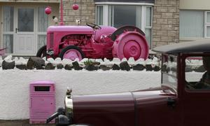 A tractor painted pink is parked on a driveway beside the stage 2 route of the Giro d'Italia that passes the village of Ballintoy, Northern Ireland, Tuesday May 6, 2014. Many towns and villages across Ireland have been going pink in preperation for the Giro d'Italia which has three stages in Ireland running from May 9-11. (AP Photo/Peter Morrison)