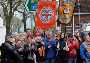 Supporters applaud as members of the Apprentice Boys of Derry and band walk past the Nationalist Ardoyne during on the way to their Easter Monday parade. William Cherry/Presseye