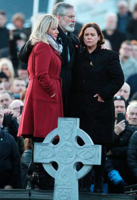 (left to right) Sinn Fein's Michelle O'Neill, Gerry Adams and Mary Lou McDonald huddle at Derry City Cemetery, in Londonderry, after the funeral service of Northern Ireland's former deputy first minister and ex-IRA commander Martin McGuinness. PA