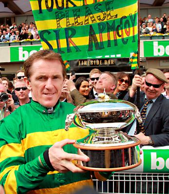 Northern Irish jockey Tony McCoy holds up the jockey championship cup presented to him on his retirement at Sandown Park Racecourse in Esher, Southern England, on April 25, 2015. Tony McCoy brings the curtain down on his record-breaking career on the aptly-named Box Office in front of a forecast full house at Sandown today. AFP PHOTO / SEAN DEMPSEYSEAN DEMPSEY/AFP/Getty Images
