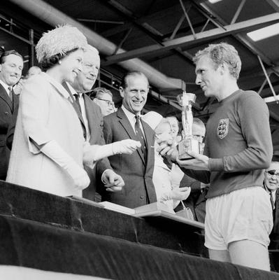 File photo dated 30/07/1966 of England captain Bobby Moore holding the Jules Rimet Trophy, collected from the Queen Elizabeth II, after leading his team to a 4-2 victory over West Germany, in an exciting World Cup Final that went to extra time at Wembley, London as the Queen turns 90 on the April 21st.PRESS ASSOCIATION Photo. Issue date: Sunday April 3, 2016. See PA story ROYAL Birthday. Photo credit should read: PA Wire