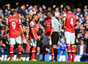 LONDON, ENGLAND - MARCH 22: Alex Oxlade-Chamberlain of Arsenal appeals to Referee Andre Marriner after he gave Kieran Gibbs of Arsenal (not pictured) a red card during the Barclays Premier League match between Chelsea and Arsenal at Stamford Bridge on March 22, 2014 in London, England.  (Photo by Richard Heathcote/Getty Images)