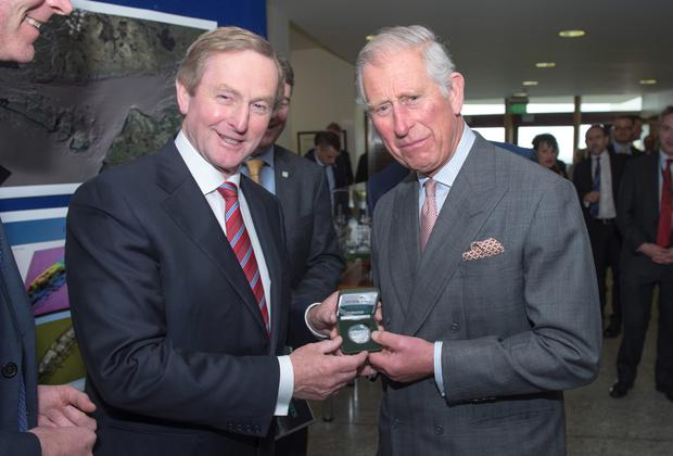 Taoiseach Enda Kenny (left) presents the Prince of Wales (right) with a limited edition commemorative medal in honour of John Philip Holland, Irish inventor of the modern submarine, at the Marine Institute in Galway, on day one of a four day visit to Ireland with the Duchess of Cornwall. PRESS ASSOCIATION Photo. Picture date: Tuesday May 19, 2015. See PA story ROYAL Ireland. Photo credit should read: Arthur Edwards/The Sun/PA Wire