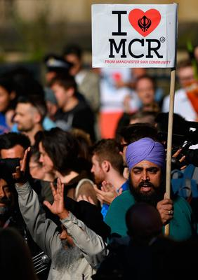 """People from Manchester Sikh Community carry """"I love MCR"""" banners as they arrive to attend a vigil in Albert Square in Manchester, northwest England on May 23, 2017, in solidarity with those killed an injured in the May 22 terror attack at the Ariana Grande concert at the Manchester Arena. Twenty two people have been killed and dozens injured in Britain's deadliest terror attack in over a decade after a suspected suicide bomber targeted fans leaving a concert of US singer Ariana Grande in Manchester. British police on Tuesday named the suspected attacker behind the Manchester concert bombing as Salman Abedi, but declined to give any further details. / AFP PHOTO / Ben STANSALLBEN STANSALL/AFP/Getty Images"""