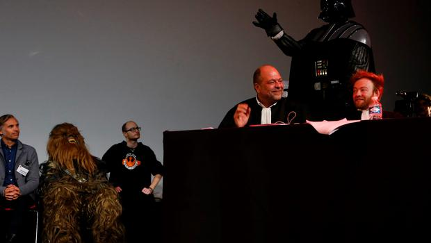 """French lawyers Eric Dupond-Moretti (C) and Antoine Vey (R) sit next to a person wearing a Darth Vader (Dark Vador) costume during the """"Darth Vader's trial"""" event at the Grand Rex movie theatre in Paris, on December 14, 2015, two days ahead of the premiere screening of the widely-anticipated Star Wars: The Force Awakens.  / AFP / THOMAS SAMSONTHOMAS SAMSON/AFP/Getty Images"""