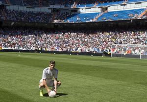 Welsh international soccer player Gareth Bale balances a ball on his head during his official presentation at the Santiago Bernabeu stadium  in Madrid, Spain, Monday, Sept. 2, 2013 after signing for Real Madrid. The Spanish club announced Sunday that Bale has signed a six-year contract, and a person familiar with the deal said the fee was a world-record €100 million ($132 million).  (AP Photo/Daniel Ochoa de Olza)