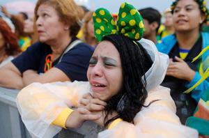 A Brazil soccer fan reacts in frustration as she watches her team play a World Cup semifinal match against Germany on a live telecast inside the FIFA Fan Fest area on Copacabana beach in Rio de Janeiro, Brazil, Tuesday, July 8, 2014. (AP Photo/Leo Correa)