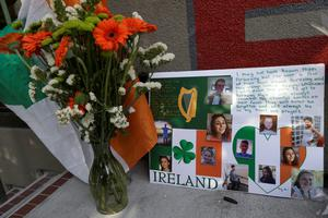 Irish flag, flowers and a sign are shown at a shrine left for victims of the Library Gardens apartment building balcony collapse Wednesday, June 17, 2015. (AP Photo/Jeff Chiu)