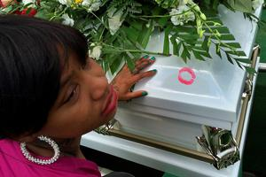 BALTIMORE, MD - APRIL 27:  A young woman leaves a lipstick print after kssing Freddie Gray's casket before it is lowered into the ground at Woodlawn Cemetery April 27, 2015 in Baltimore, Maryland. Gray, 25, was arrested for possessing a switch blade knife April 12 outside the Gilmor Homes housing project on Baltimore's west side. According to his attorney, Gray died a week later in the hospital from a severe spinal cord injury he received while in police custody.  (Photo by Chip Somodevilla/Getty Images)