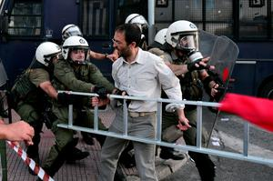 An anti-EU protester scuffles with police outside the European Comission offices in Athens on July 2, 2015.  Greece's government and international creditors raised the stakes on July 2 over a weekend referendum seen as decisive for the nearly insolvent EU country's political and financial future. While Prime Minister Alexis Tsipras has urged Greeks to vote 'No' to the austerity measures demanded by international creditors, opposition parties including the centre-right New Democracy are campaigning for a 'Yes' vote in the referendum on July 5.  AFP PHOTO / Louisa GouliamakiLOUISA GOULIAMAKI/AFP/Getty Images